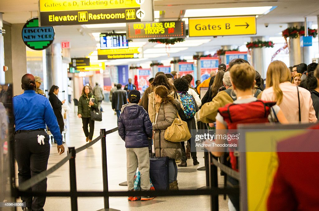 Travelers wait in line outside a boarding gate on Thanksgiving Day November 27 2014 at LaGuardia Airport in the Queens borough of New York City New...