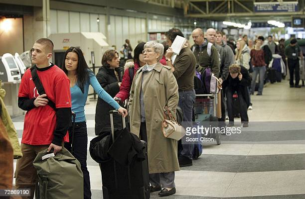 Travelers wait in line to check in at O'Hare International Airport December 22 2006 in Chicago Illinois Airlines were forced to play catchup on this...