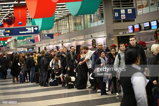 Travelers wait in line to checkin for flights at O'Hare International Airport on December 20 2013 in Chicago Illinois More than 200000 passengers are...
