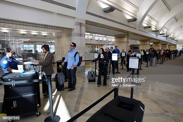 Travelers wait in line to pass through security including a new body scanner at John Wayne Airport's new Terminal C Five new security screening lanes...