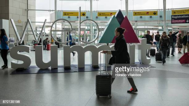 Travelers walk by a large sign advertising Web Summit in Terminal 1 during the first registration day at the city's international airport on November...