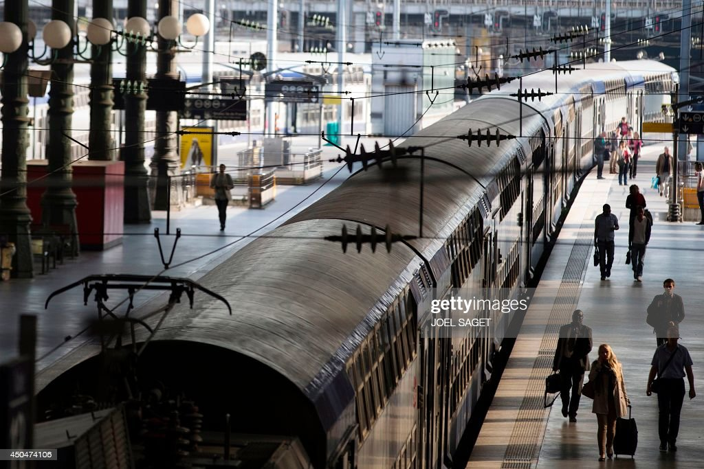 Travelers walk on a platform at the Gare du Nord railway station on June 12 2014 in Paris on the second day of a national strike by French SNCF...