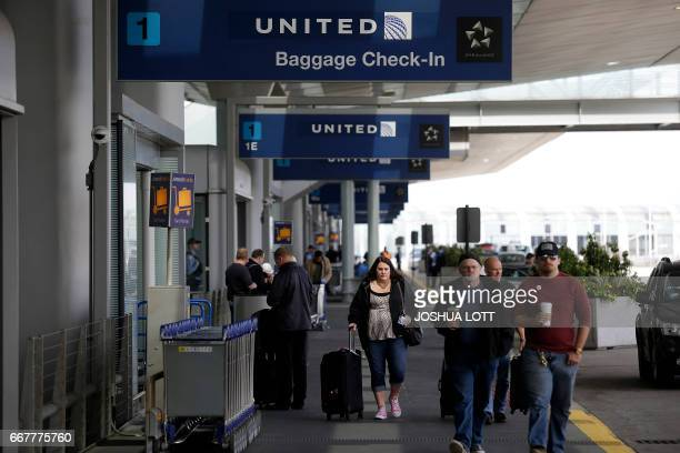 Travelers walk outside the United Airlines terminal at O'Hare International Airport on April 12 2017 in Chicago Illinois United Airlines has been...