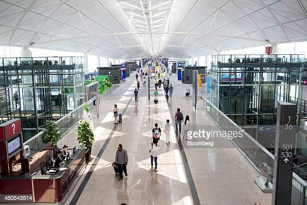 Travelers walk past departure gates at Hong Kong International Airport in Hong Kong China on Friday June 13 2014 American Airlines Group Inc...