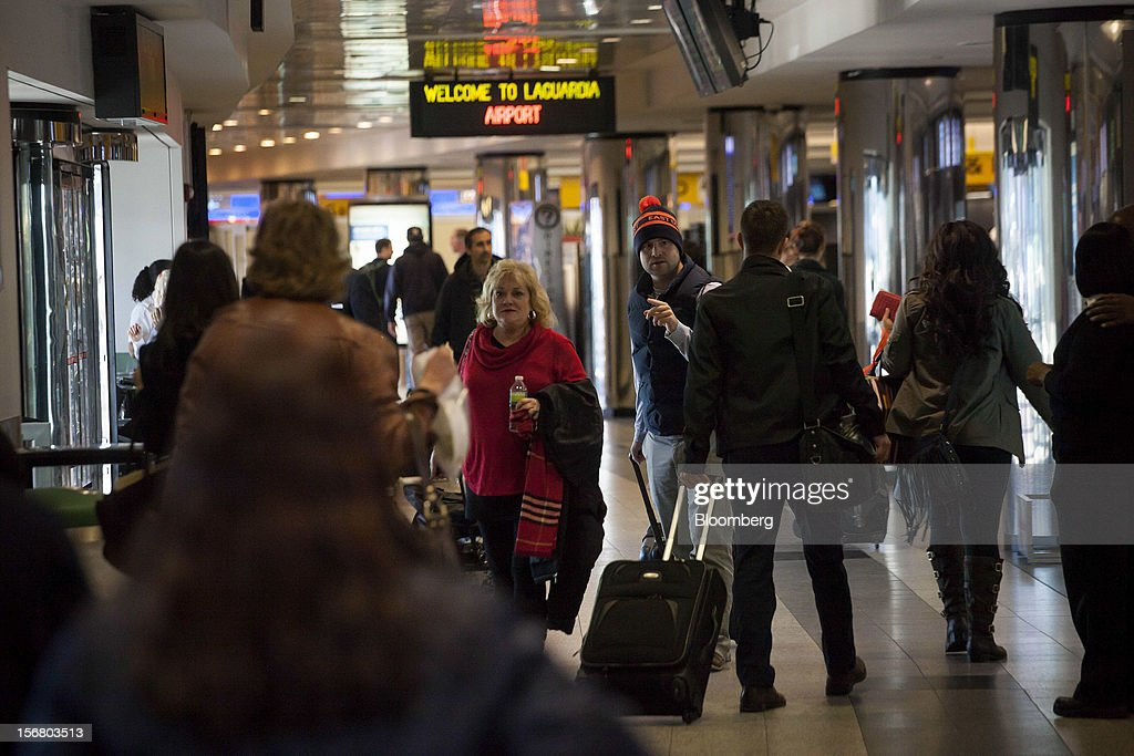 Travelers walk through Terminal B at LaGuardia Airport in the Queens borough of New York, U.S., on Wednesday, Nov. 21, 2012. U.S. travel during the Thanksgiving holiday weekend will rise a fourth straight year, gaining 0.7 percent from 2011, as trips by automobile rise even as airplane trips decline, AAA said last week. Photographer: Michael Nagle/Bloomberg via Getty Images