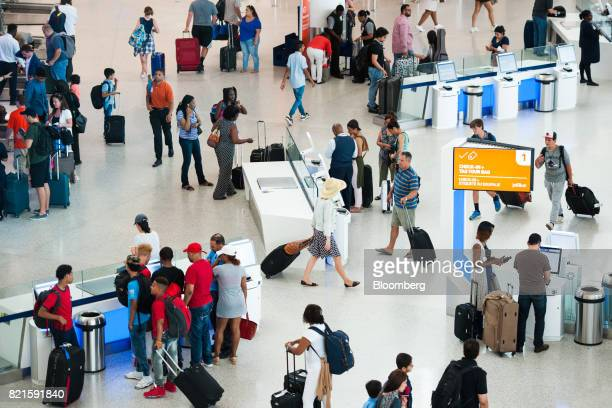 Travelers walk through the JetBlue Airways Corp Terminal 5 at John F Kennedy International Airport in New York US on Wednesday July 12 2017 Jetblue...