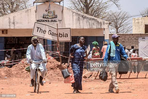 Travelers walk through the SenegaleseGambia border town of Keur Ayip in Senegal on May 9 2016 Senegal and the Gambia have agreed to hold talks on May...