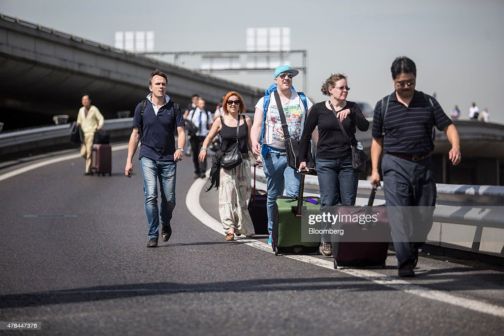 Travelers walk with their luggage on a road near Charles de Gaulle airport as French cab drivers protest against Uber Technologies Inc.'s car sharing service in Roissy, France, on Thursday, June 25, 2015. French taxi drivers are on indefinite nationwide strike as they demand a government crackdown on what they say is Uber's use of unlicensed chauffeurs for its UberPop service. Photographer Balint Porneczi/Bloomberg via Getty Images