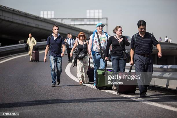 Travelers walk with their luggage on a road near Charles de Gaulle airport as French cab drivers protest against Uber Technologies Inc's car sharing...