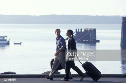 Travelers Walking With Suitcases Along The Harbor : Stock Photo