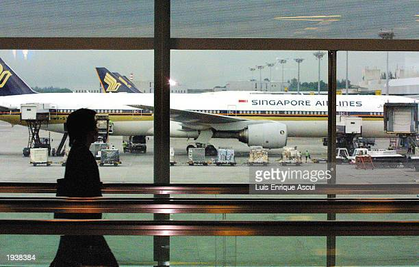Travelers wear masks to protect themselves from getting SARS April 18 2003 at Singapore's Changi Airport in Singapore To further contain the spread...
