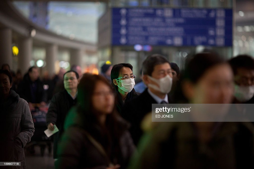 Travelers wearing face masks arrive at Beijing's international airport on January 23, 2013. China's capital Beijing will strengthen measures to combat pollution, state media reported, amid public anger over the dangerous air quality in the sprawling metropolis. AFP PHOTO / Ed Jones