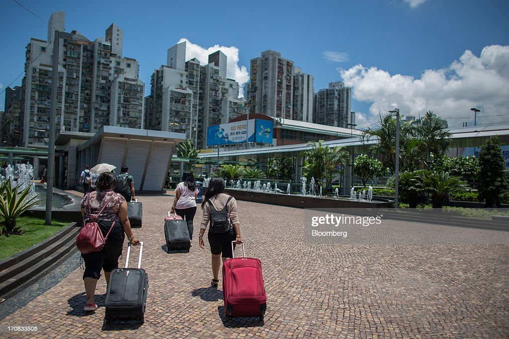 Travelers with their bags leave the Zhuhai-Macau border crossing in Macau, China, on Tuesday, June 18, 2013. Casino revenue in Macau, the only place in China where casino gambling is legal, rose 14 percent to a record of 304 billion patacas ($38 billion) in 2012. Photographer: Lam Yik Fei/Bloomberg via Getty Images