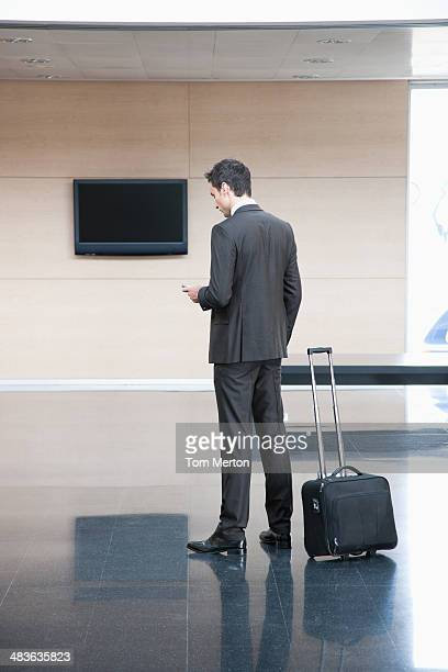 Traveling businessman checking cell phone