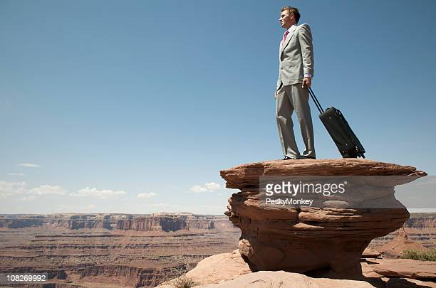 Traveling Businessman Standing Outdoors with Suitcase on Mesa Overlook