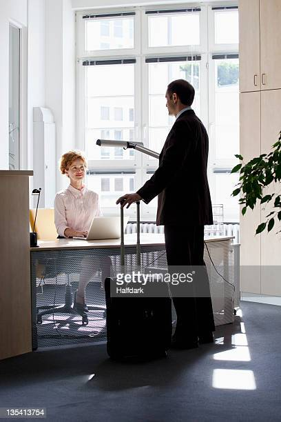 A traveling businessman talking to a businesswoman sitting at a desk