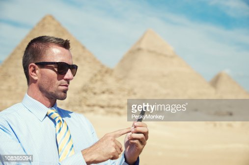 Traveling Businessman Using Smartphone at Egyptian Pyramids : Bildbanksbilder