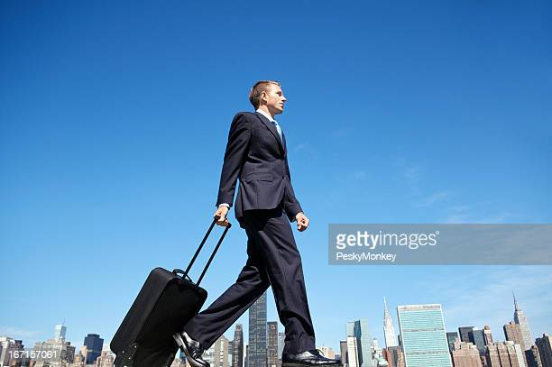 Traveling Businessman Walking with Suitcase Across City Skyline