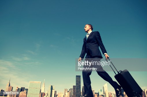 Traveling Businessman Wheeling Suitcase Across City Skyline : Stock Photo