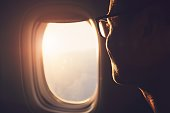 Young passenger looking out through window of the airplane during sunrise.