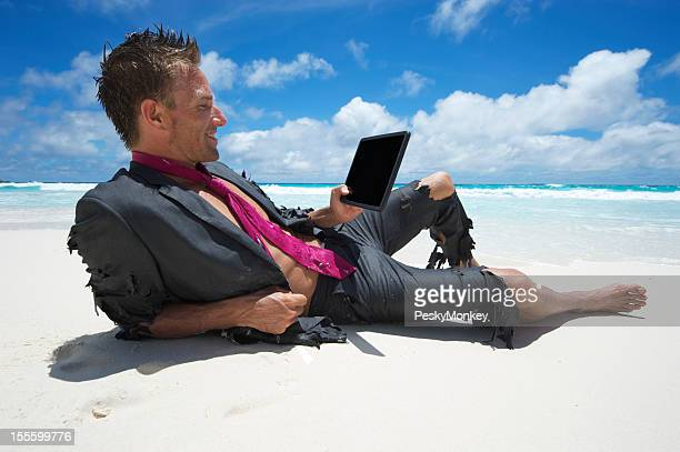 Traveling Castaway Businessman Relaxing with Digital Tablet on Beach