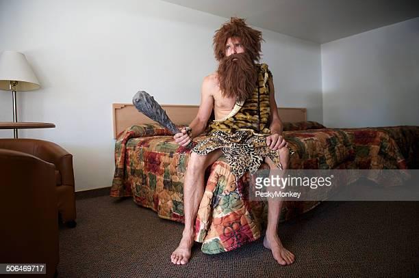 Voyager Homme des carvernes assis sur Old Fashioned Motel lit de la chambre