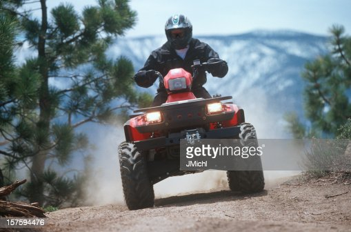 ATV traveling down a dust mountain trail.