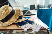 close up view of hats, passports with tickets and american flag on wooden chair at airport