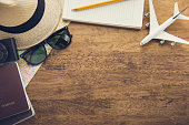 Traveling gadgets including camera,  map, notebook, passport, sunglasses and airplane model on wood table background, top view border design with copy space