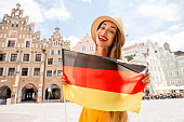 Portrait of a young female tourist with german flag on the bavarian old town background in Landshut.