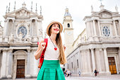 Young female tourist standing on the famous San Carlo square in Turin city. Traveling in Piedmont region in Italy