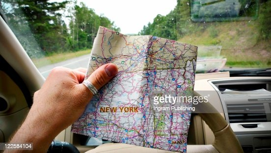 Traveling man looking at map of New York in car, while on road trip. : Foto de stock