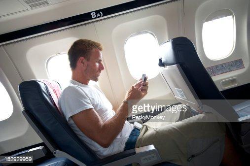 Viaje hombre sentado enviando mensajes de texto por teléfono móvil en el asiento de avión