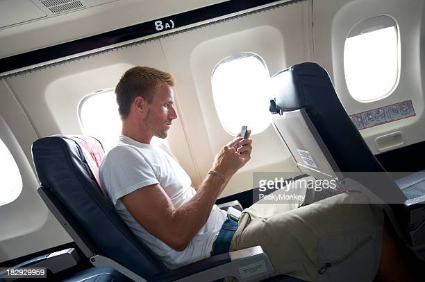 Traveling Man Sitting Texting on Mobile Phone in Airplane Seat