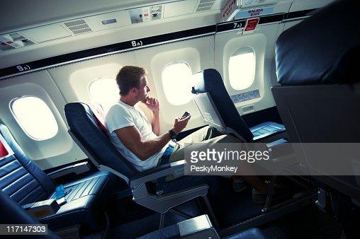 Viajando hombre sentado con Smartphone asiento de pequeña ventana de avión