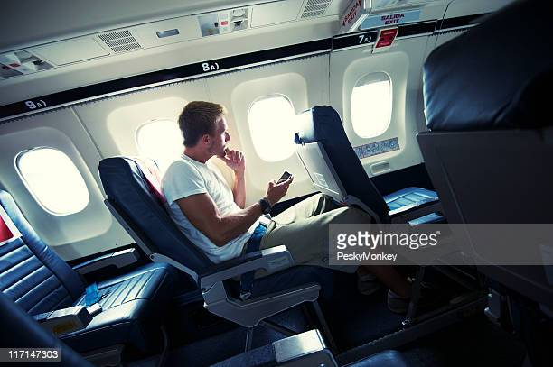 Traveling Man Sitting With Smartphone Window Seat of Small Airplane