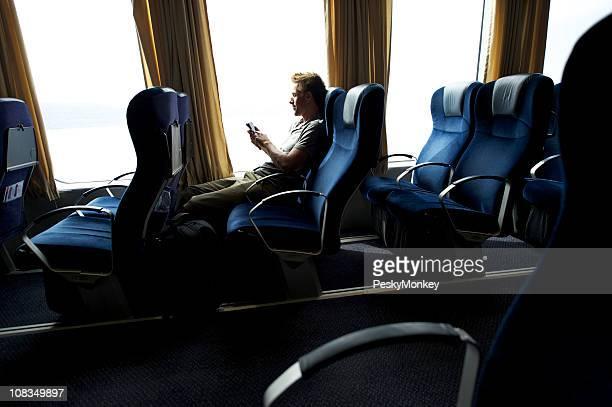 Voyager homme utilisant un Smartphone SMS dans le siège près de la fenêtre