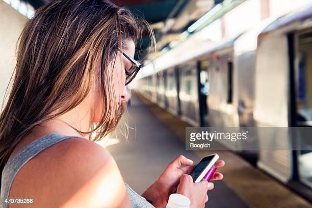 Femme voyageant à New York à envoyer des SMS, vous attend pour métro plate-forme