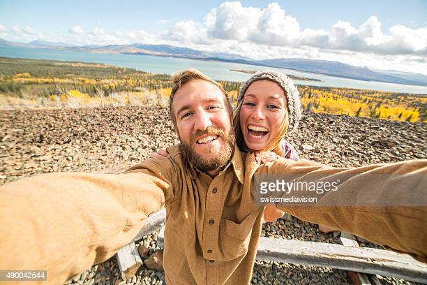 Traveling young couple taking selfie on mountain top