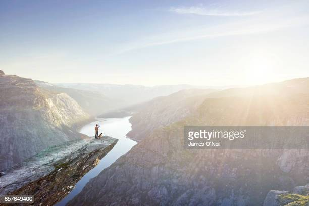 Traveller and dog looking out from cliff edge, Trolltunga, Norway