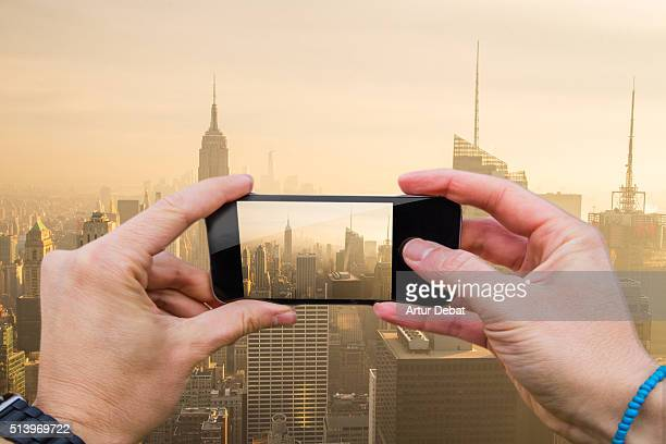 Traveller man taking pictures with smartphone from personal point of view from top of the Manhattan city on sunset and the Empire State Building.