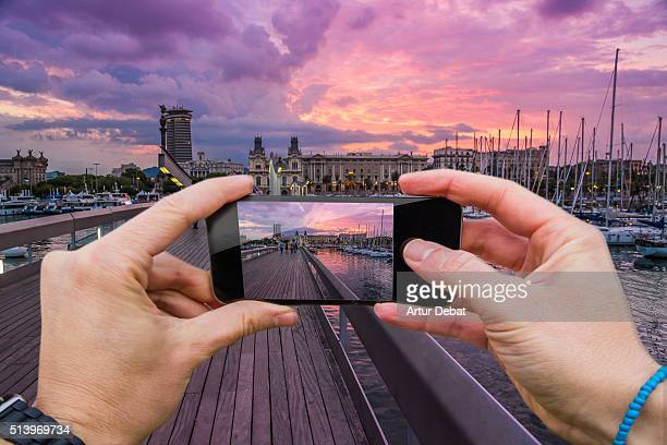 Traveller man taking pictures with smartphone from personal point of view of the colorful sunset over the Barcelona city from the harbor.