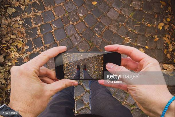 Traveller man taking pictures with smartphone from personal point of view of his legs of the cobble stone pavement in the Turin city with autumn leafs.