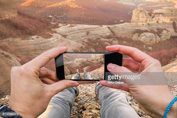 Traveller man taking pictures with smartphone from personal point of view of his legs contemplating the stunning landscape from summit in the Catalan Pyrenees.