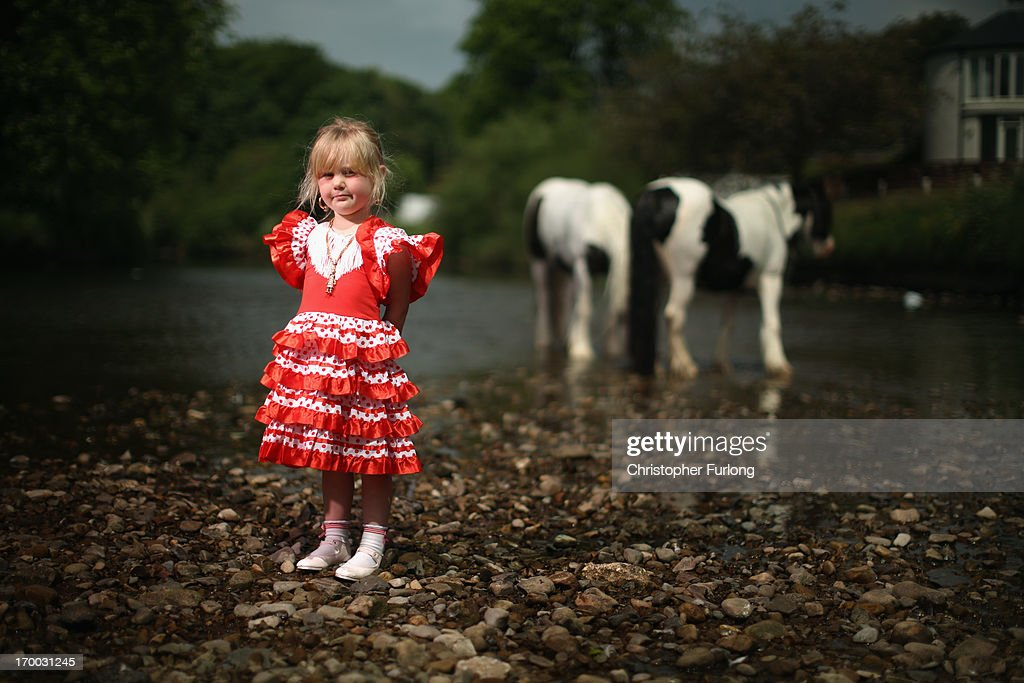 Traveller Milly Edwards, aged 3, poses next to the River Eden during the Appleby Horse Fair on June 6, 2013 in Appleby, England. The Appleby Horse Fair has existed under the protection of a charter granted by James II since 1685 and is one of the key gathering points for the Romany, gypsy and traveling community. The fair is attended by about 5,000 travellers who come to buy and sell horses. The animals are washed and groomed before being ridden at high speed along the 'mad mile' for the viewing of potential buyers.