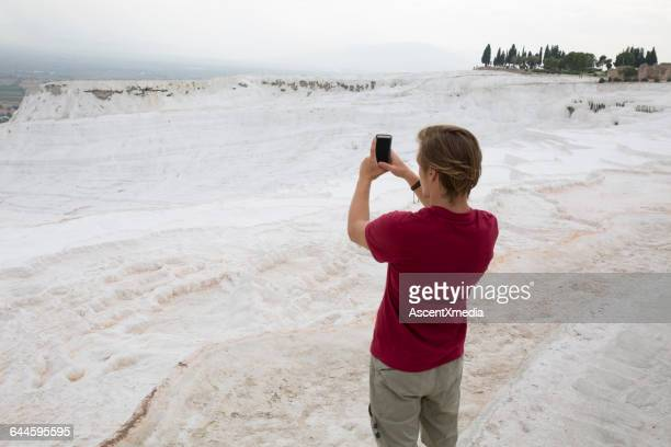 Traveller takes photo of white travertine terraces