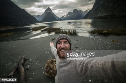 Traveller takes selfie at Milford sound, New Zealand : Stock Photo