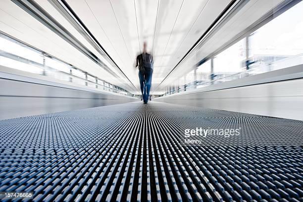 Traveller walking on moving stairway airport walkway
