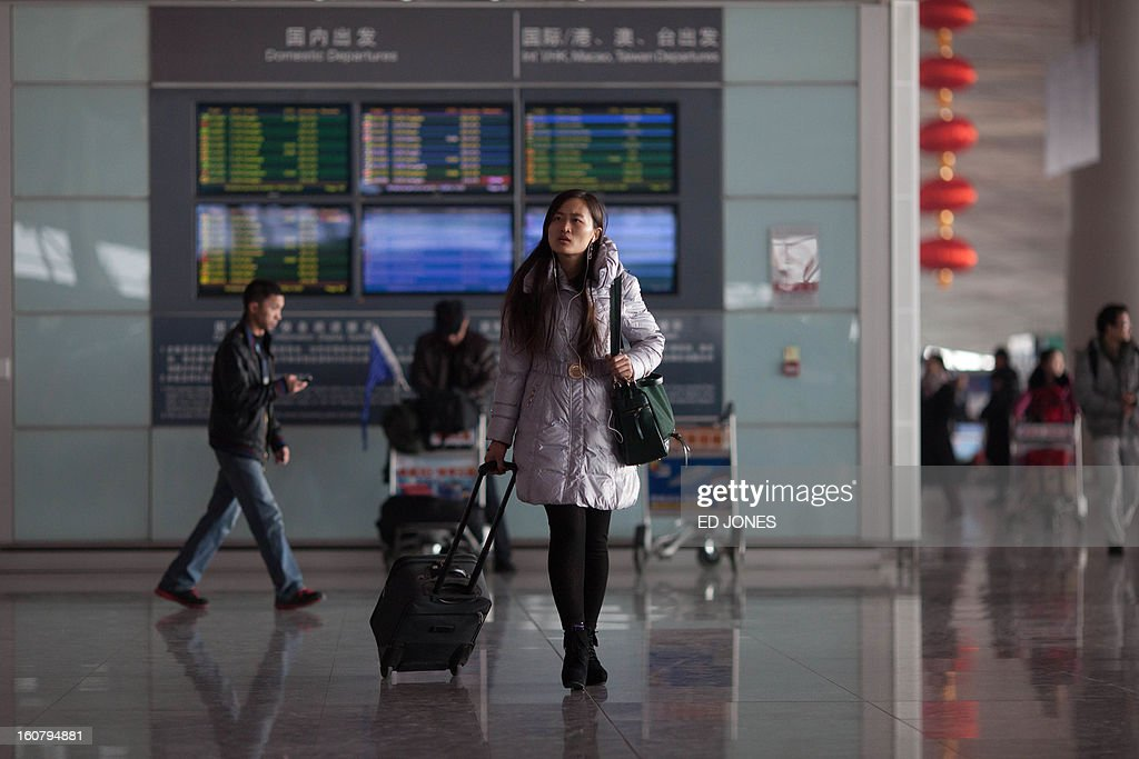 A traveller walks past a departures information board at Beijing's international airport on February 6, 2013. China is preparing to welcome the Lunar New Year, or Spring Festival, which falls on Febraury 10. AFP PHOTO / Ed Jones