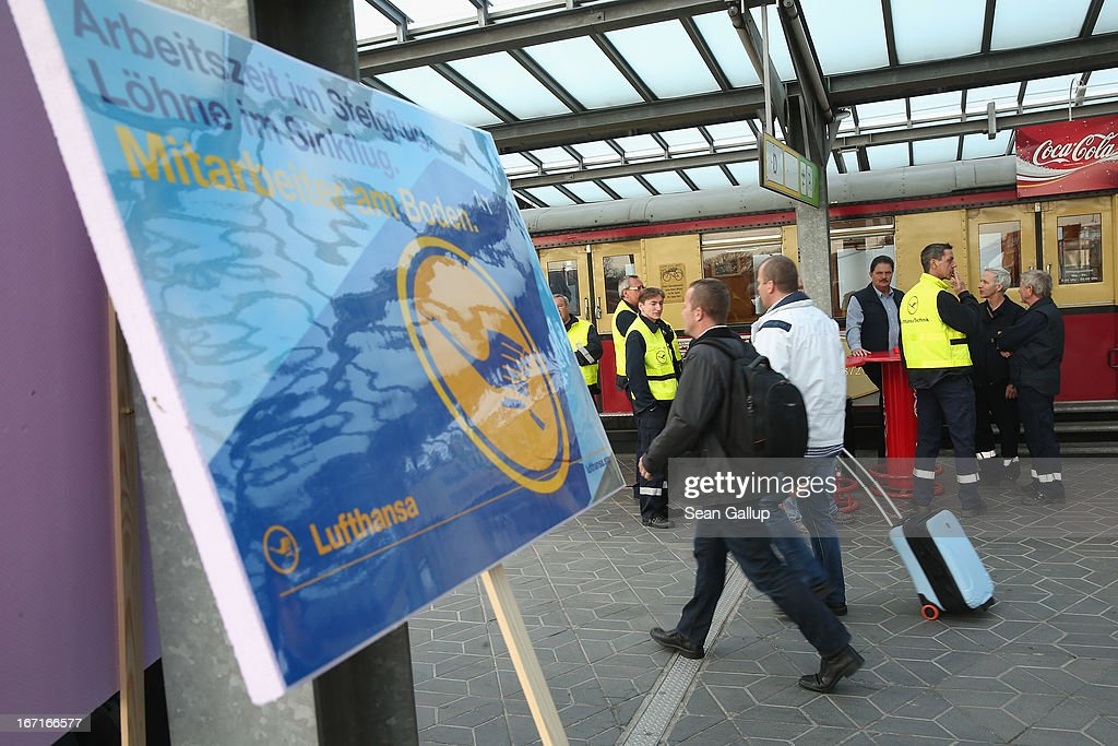 A traveller walks past striking Lufthansa employees and a protest sign at Tegel Airport during a nationwide strike by Lufthansa ground, service and maintenance personnel on April 22, 2013 in Berlin, Germany. Workers are demanding pay raises and job guarantees and today's strike has forced Lufthansa to cancel approximately 1700 flights.